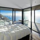 Спальня с полностью остекленными стенами и видом на океан.