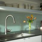 Кухонный фартук за кухонной раковиной выполнен из матового стекла и именно он формирует интересный полупрозрачный проем в гостиной.