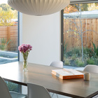 Просторная и светлая столовая с большой площадью остекления. Деревянная ограда добавляет приватности.