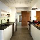 Современная кухня с новой бытовой техникой отлично вписалась в модернистский дом середины прошлого века.