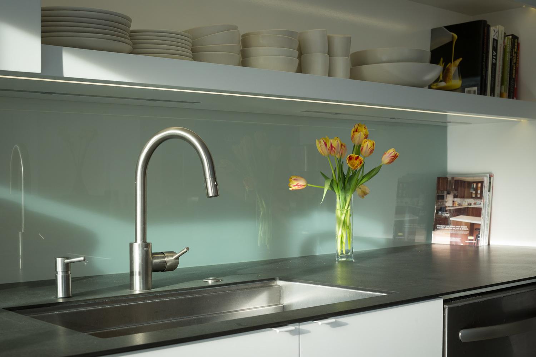 Кухонный фартук за кухонной раковиной выполнен из матового стекла и именно он формирует интересный полупрозрачный проем в гостиной