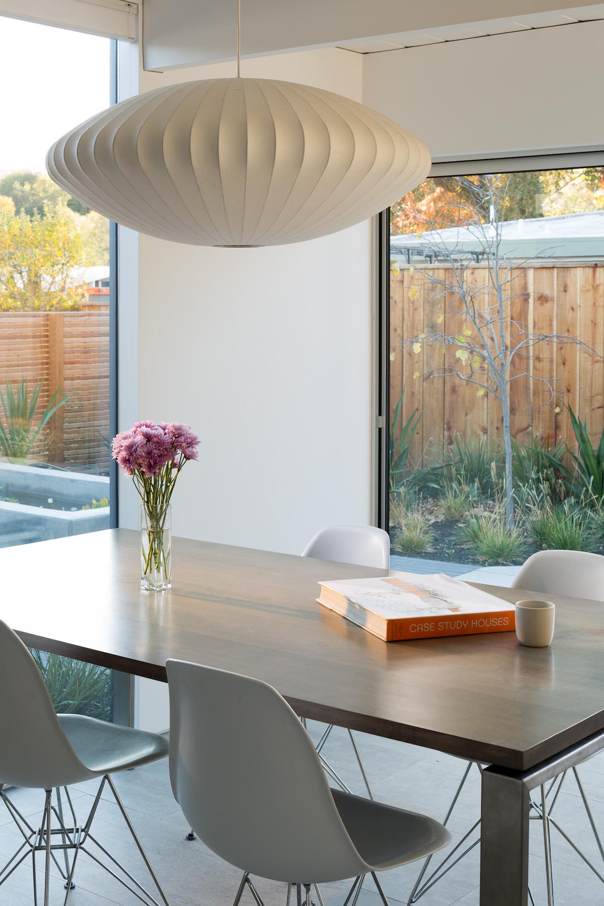 Просторная и светлая столовая с большой площадью остекления. Деревянная ограда добавляет приватности