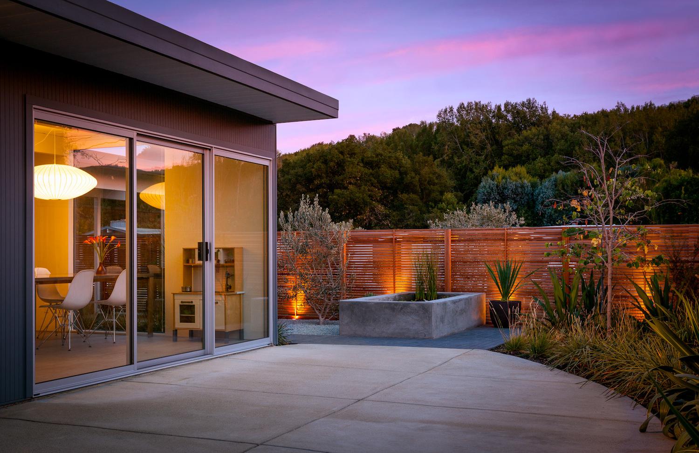Терраса за домом. Подсвеченный деревянный забор отлично смотрится в вечернее время.