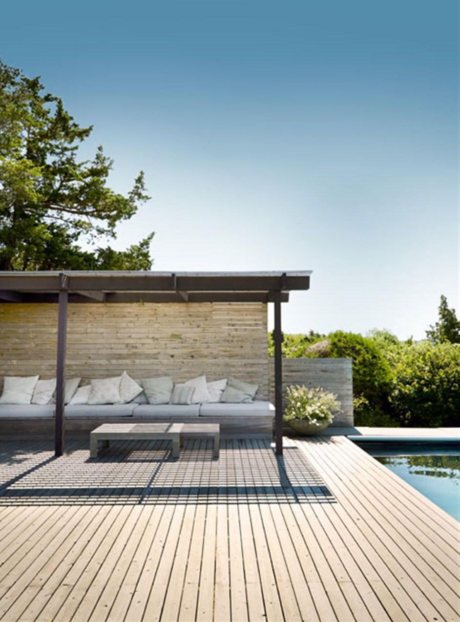 Большая деревянная терраса рядом с бассейном. От солнца можно укрыться на диванчике под перголой.