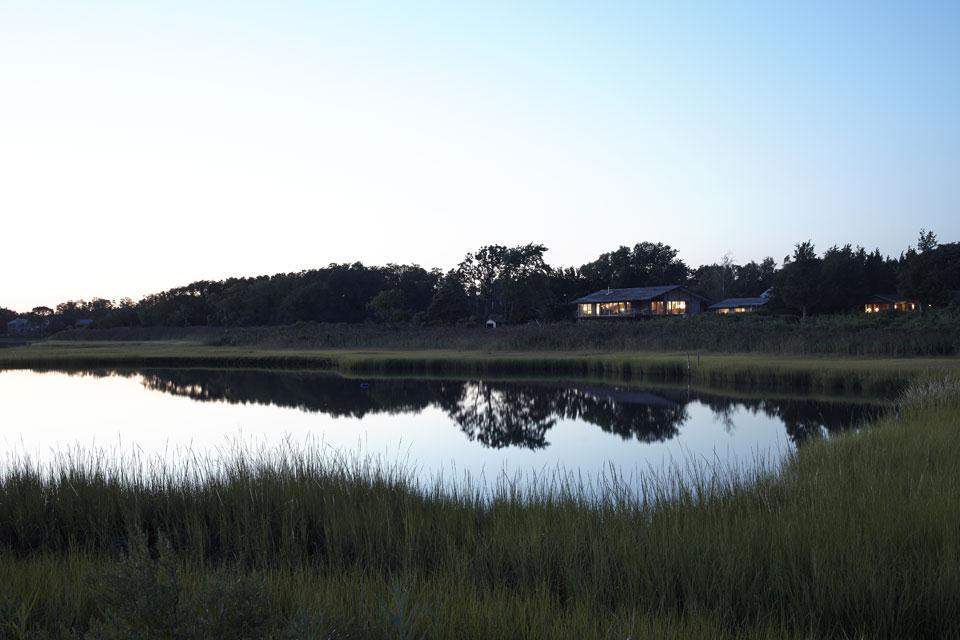 Большой дом отлично вписывается в зеленый ландшафт на берегу залива.