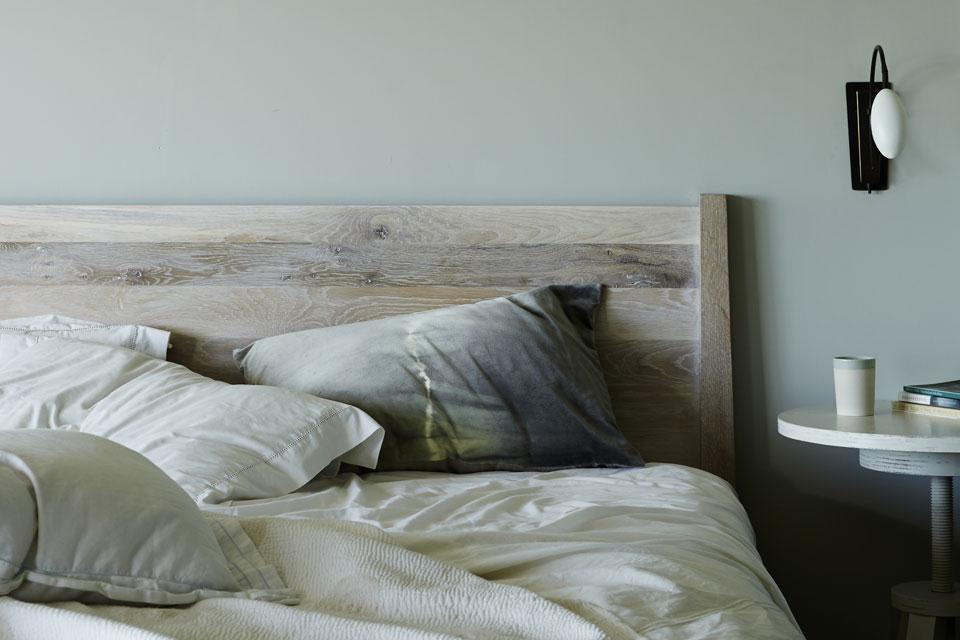 Спальня выдержана в спокойных сдержанных тонах. Интересный круглый прикроватный столик на винтовой ножке лишь частично попал на фото.