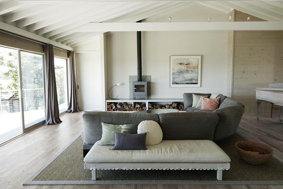 Светлая гостиная с камином и отделкой отбеленным деревом. Стропильные конструкции оставлены открытыми и украшают помещение.