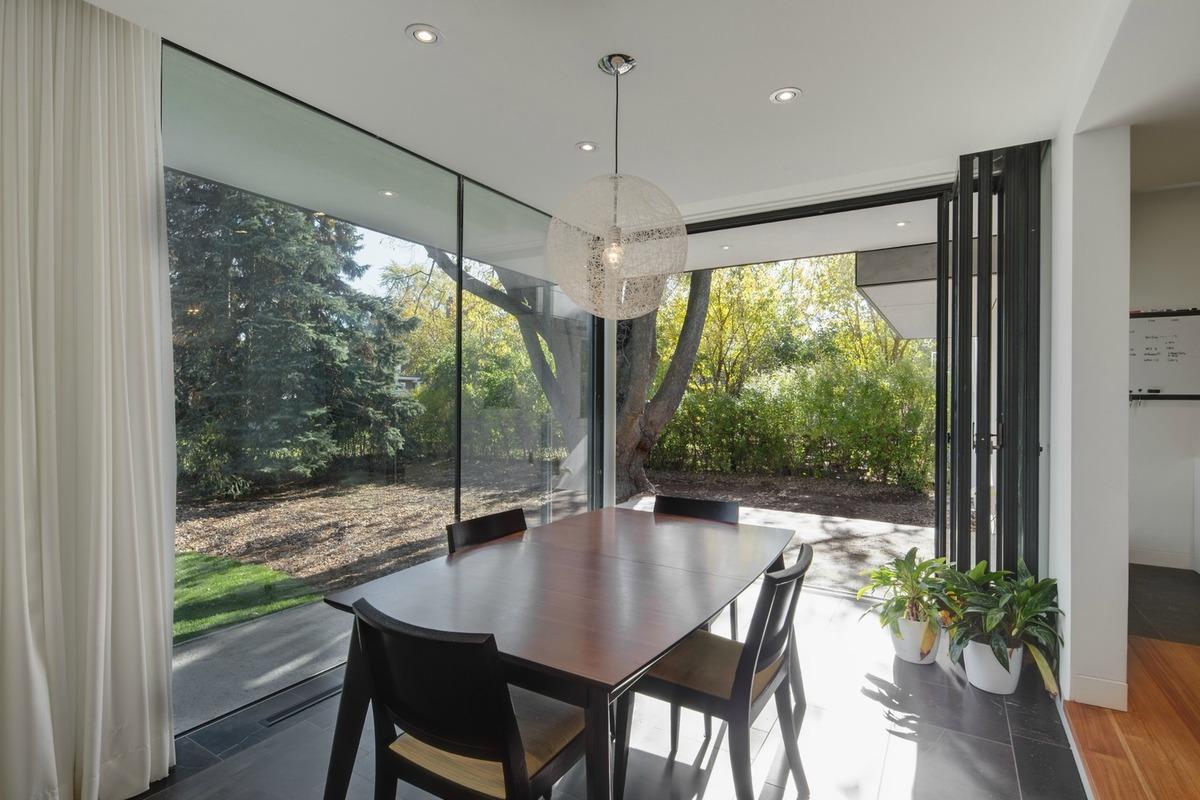 Сдвижные стеклянные двери-гармошка ведут в сад.