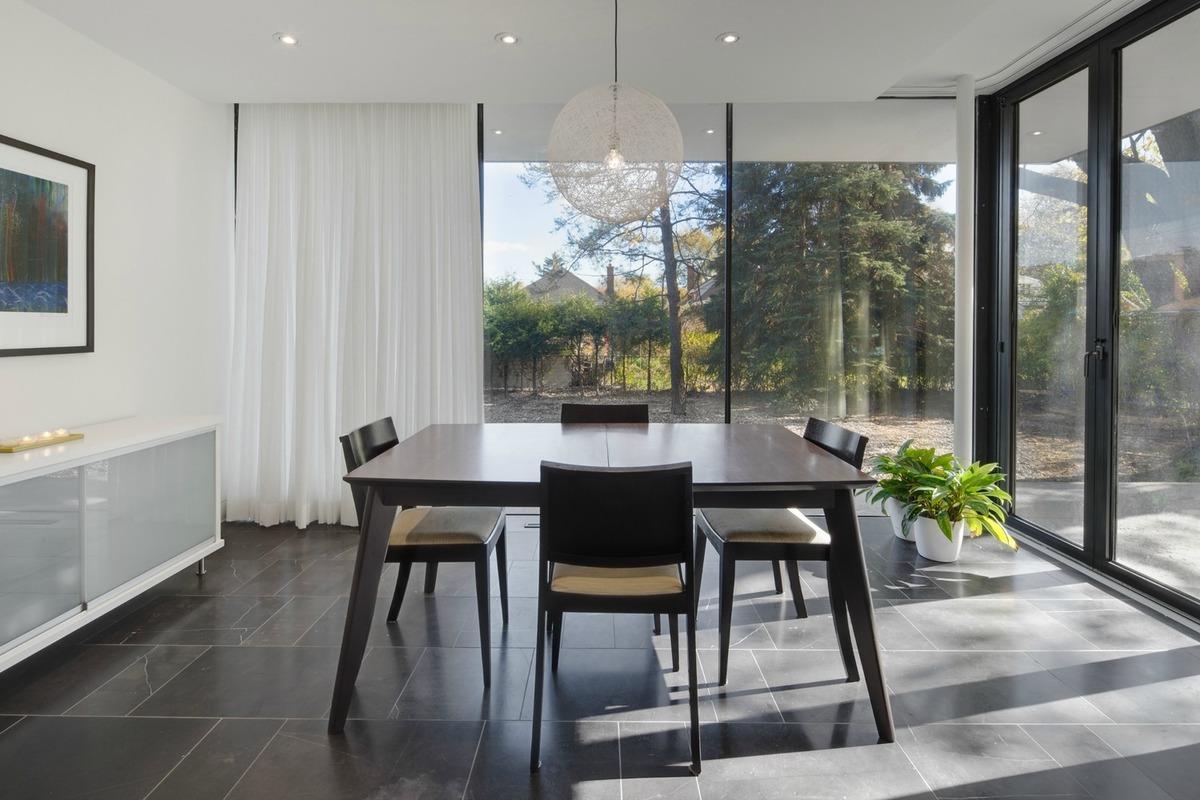 Столовая тесно связана с садом благодаря остекленным стенам. Занавески могут добавить приватности, когда это необходимо.