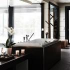 Цветы и свечи рядом с гидромассажной ванной в ванной комнате рядом с сауной.