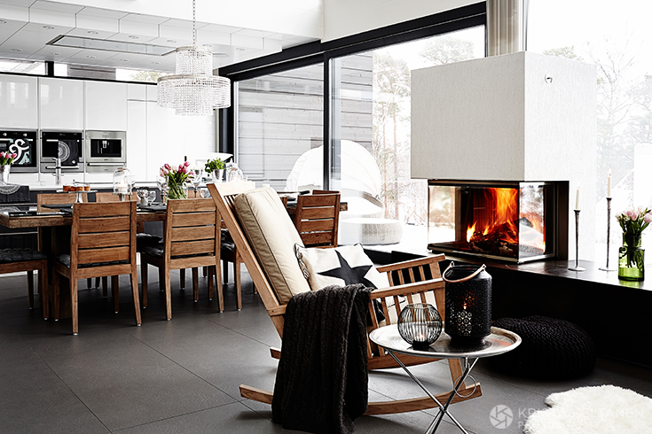 Камин визуально разделяет столовую и гостиную. Гостиную также украшают разнообразные подсвечники.