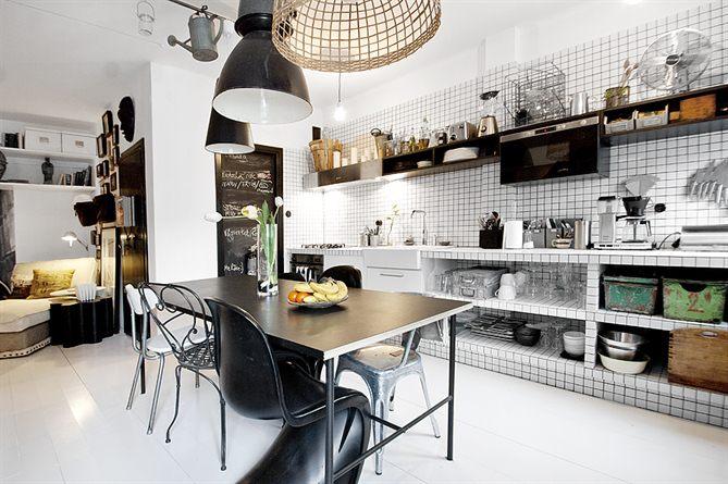 Необычно смотрятся открытые полки обложенные кафельной плиткой под кухонной столешницей обложенной такой же белой кафельной плиткой. Конечно не так необычно как висящая под потолком садовая лейка.