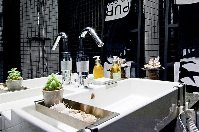 Ванна в черно-белых тонах и тем же кафелем что на кухне. Особого внимания заслуживают стальные крючки для полотенец на умывальнике и стальная полочка с декором.