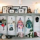 Традиционно организованная и оформленная прихожая. У каждого ребенка есть своя секция, а на верхней полке разместили фотографии и декор.