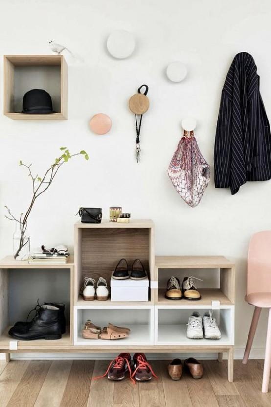 Современная прихожая с очень удобными крючками для одежды и трансформируемым шкафчиком состоящим из отдельных секций.