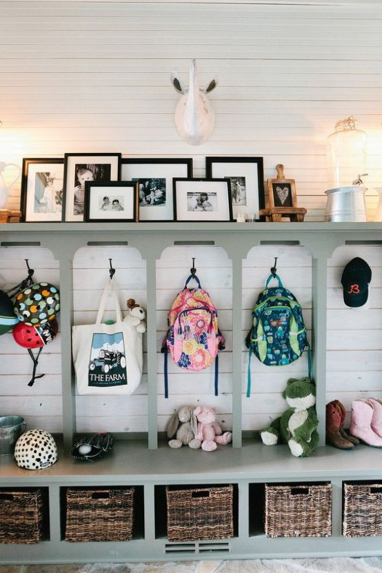 Традиционно организованная и оформленная прихожая. У каждого ребенка есть своя секция, а на верхней полке разместили фотографии и декор