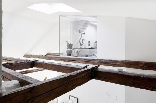 На фото хорошо видны балки старой стропильной конструкции, мансардное окно делающее гостиную еще светлее. На заднем плане видно остекленную спальню родителей.