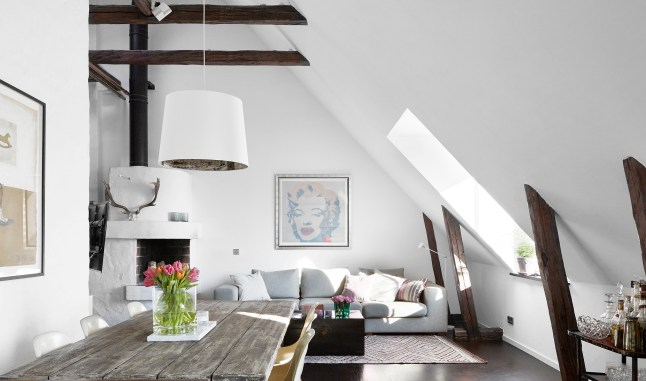 Высокая и светлая гостиная с наклонными стенами.