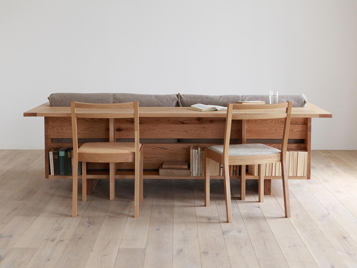 Под столом вдоль всей спинки дивана выполнена книжная полка.
