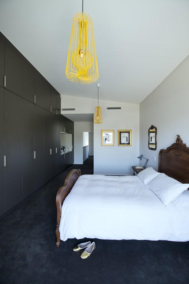 Деревянная кровать в стиле барокко, видимо, должна была стать центральным объектом этой эклектичной спальни. При этом минималистичный шкаф вдоль всей стены не должен отвлекать внимания от центрального объекта - кровати.