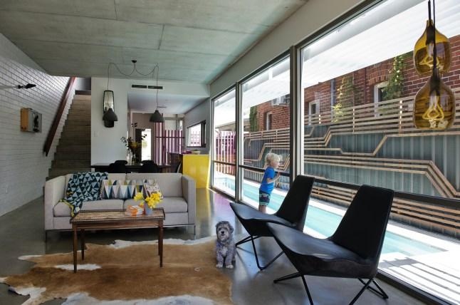 Гостиная, столовая и кухня имеют открытую планировку и хорошо освещены благодаря остекленной стене, которая выходит к бассейну и декорированному забору.