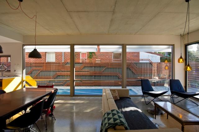 Окна, или точнее остекленная стена, гостиной выходят на забор, что не удивительно для узкого участка. Поэтому дизайнеры сделали забор украшением гостиной.