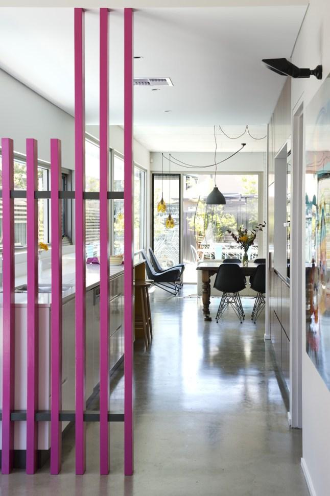 Розовый забор находящийся у входа в дом на улице дублируется перегородкой между кухней и прихожей.