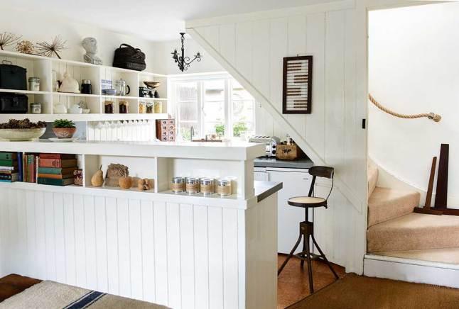 Кухня расположена под лестницей на второй этаж и отделена от столовой перегородкой чуть выше кухонной поверхности. Она скрывает столешницу и то что находится на ней от гостей в столовой, однако не изолирует того кто готовит от компании в столовой.
