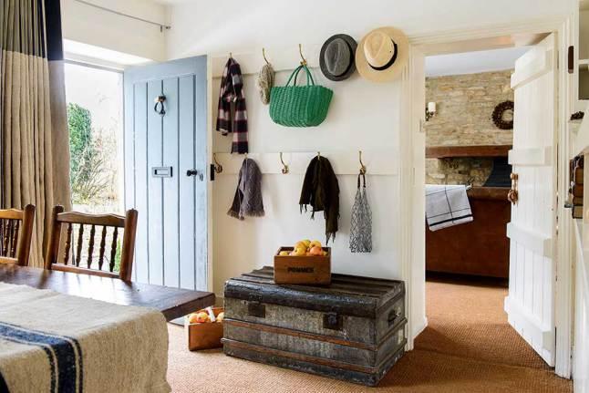 Прихожая довольно простая с крючками для одежды на стене и винтажным сундуком в качестве тумбочки.