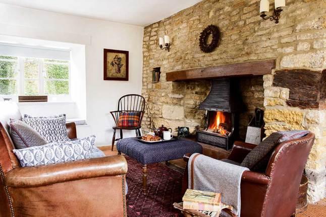 Традиционный английский дом не может обойтись без камина в гостиной. Для создания нужной атмосферы даже была оставлена неоштукатуренной стена рядом с камином.