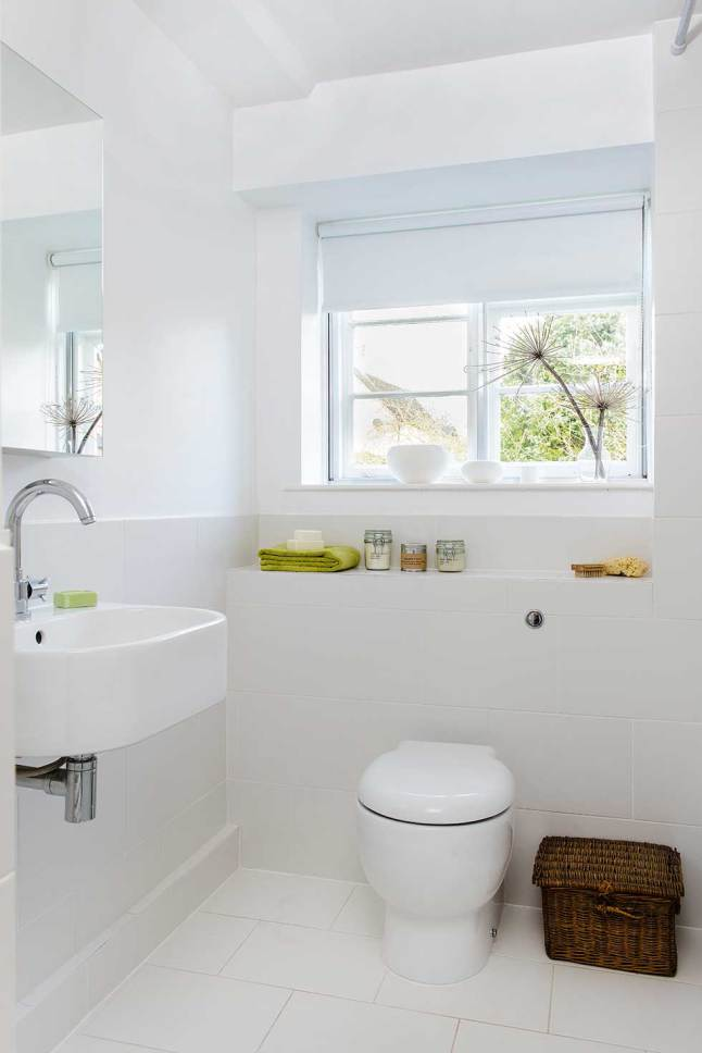 Ванная с современной сантехникой, кафелем и мебелью. Связь с интерьером дома создает плетеная корзинка в углу.