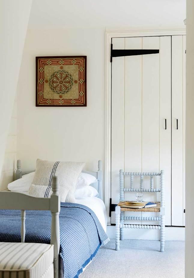 Вторая спальня с деревянной кроватью, светлыми стенами и стенным шкафом.