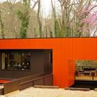 К дому ведет стальной мостик, а крыльцом служит просторная терраса.