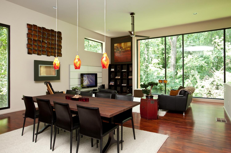 Большие окна впускают в дом естественный свет одновременно открывая вид на лесной пейзаж.