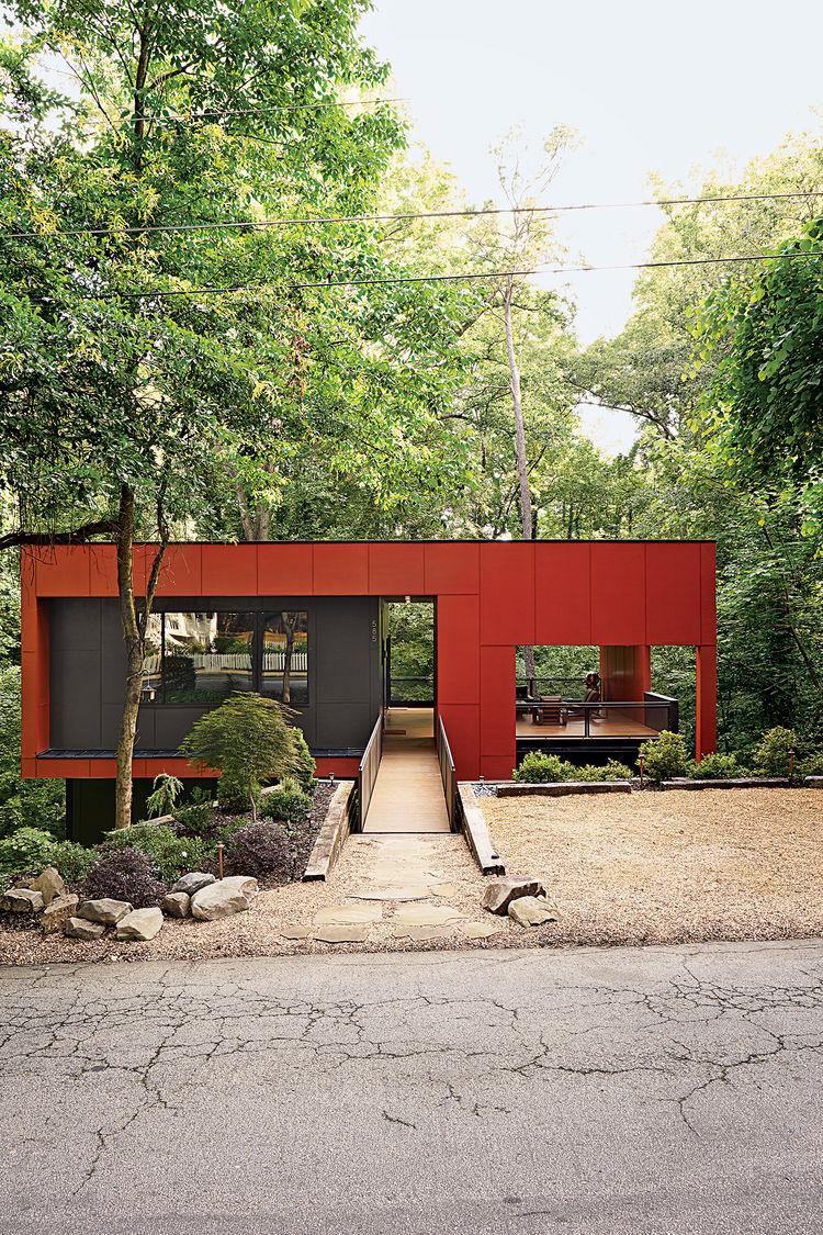 Фасад дома со стороны дороги. Дом имеет простую и привлекательную форму подчеркнутую контрастными цветами.