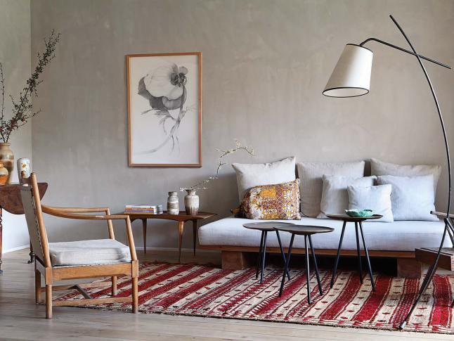 Интерьер гостиной, как и всей квартиры, выдержан в сдержанной естественной цветовой гамме с отдельными яркими акцентами, например как ковер с этническим орнаментам.
