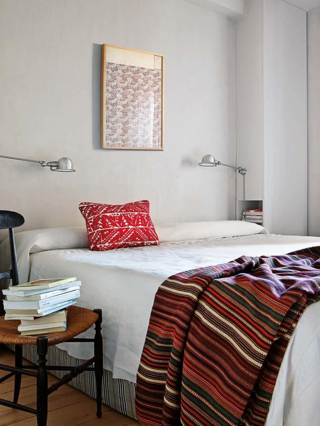Интерьер спальни минималистичен, настроение задается красочными этническими орнаментами аксессуаров.