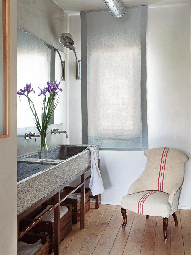 Интерьер ванной выдержан в общем стиле квартиры, с деревянным полом и вниманием к деталям. Размер ванной позволил поставить там кресло.