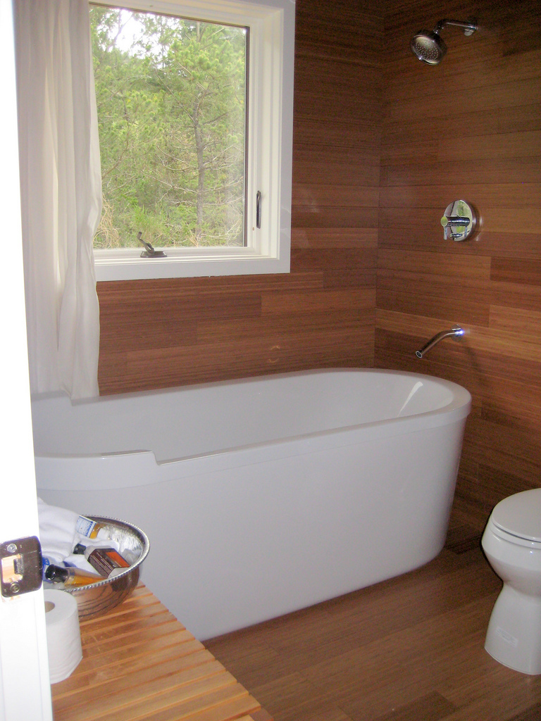 Одна из ванных комнат с ванной обшита деревом в соответствии с общим интерьером дома.