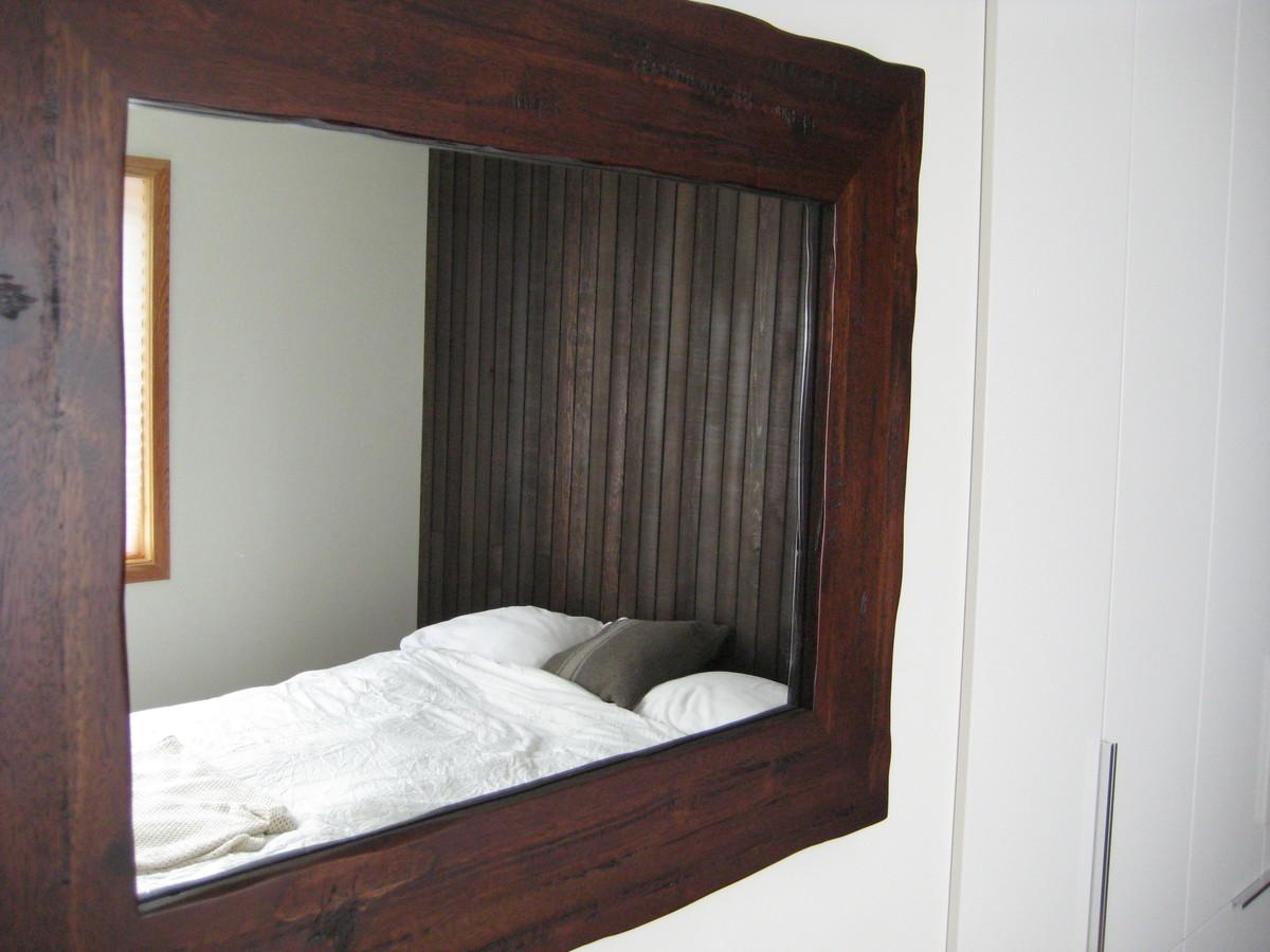 Отражение гостевой спальни в зеркале рядом с кроватью.
