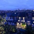 Пристройка с большой площадью остекления выгодно смотрится в вечернее и ночное время при включенном свете в доме.