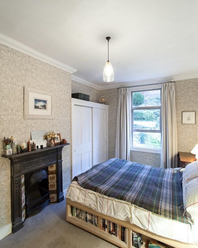 Спальня небольшая, поэтому очень рационально выглядит кровать с книжными полками под ней. Кроме того с такими полками пространство выглядит более организованным