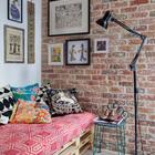 Довольно распространенное решение для интерьера в стиле лофт - мебель из палет. Заслуживают внимание картины на стенах привносящие индивидуальность в прохладный стиль интерьера.