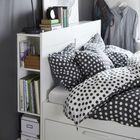 Белая кровать с выдвижными ящиками и полками в торце изголовья.