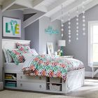 Высокая классическая кровать с ящиками и полками.