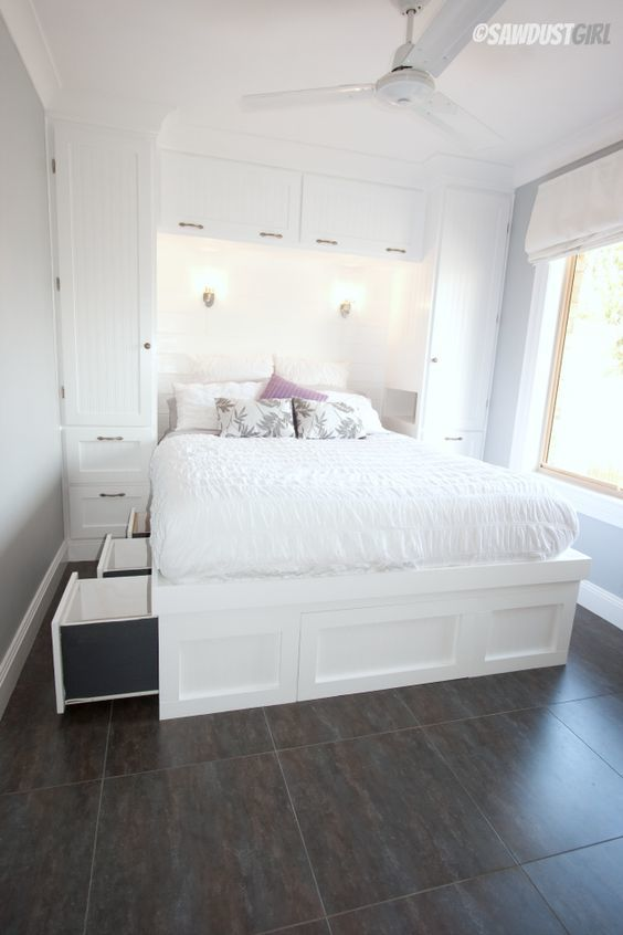Белая спальня с кроватью с ящиками и шкафами у изголовья.