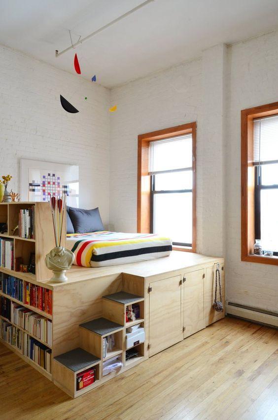 Кровать-подиум который включает в себя и систему хранения под кроватью и книжные полки отгораживающие спальное место от остальной части комнаты.