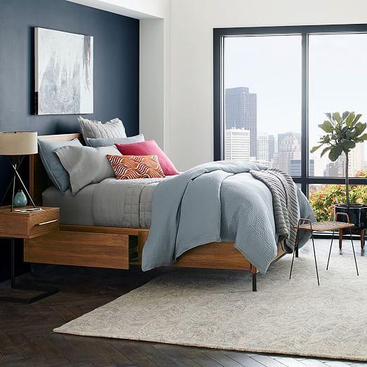 Минималистичная современная кровать с ящиками и даже на ножках, что редко встречается у кроватей с системой хранения.
