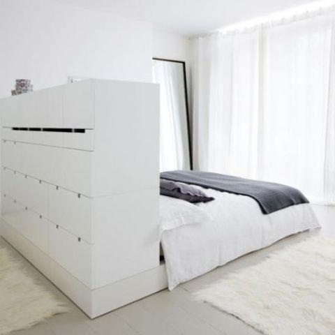 Современная белая кровать с большой системой хранения в изголовье, которая является частью гардероба.