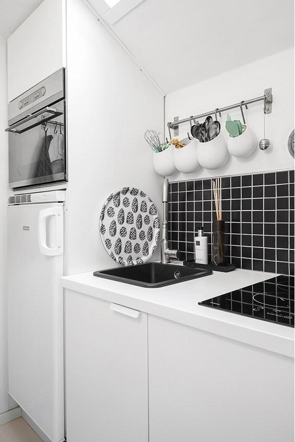 Небольшая кухня с фартуком из черной плитки.